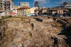 Utgrävningplatsen av en romare fördärvar sett från över med bostads- byggnader i bakgrunden arkivbild