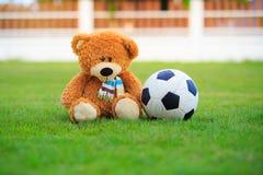 Uthärda dockan med fotboll på fältet av gräs Arkivbild