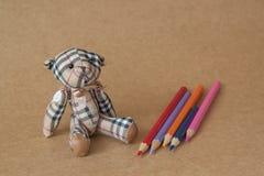 Uthärda leksaker på textur av pappers- bakgrunder och blyertspennor Fotografering för Bildbyråer