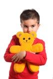 uthärda pojken som rymmer little nalle Fotografering för Bildbyråer