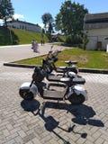 Uthyrnings- elektriska sparkcyklar som väntar på, parkerar royaltyfri foto