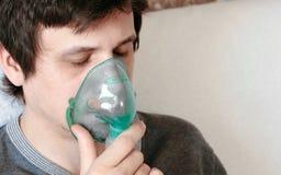 Utilice el nebulizador y el inhalador para el tratamiento Cara del ` s del hombre joven del primer con los ojos cloused que inhal Fotos de archivo