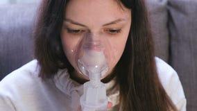 Utilice el nebulizador y el inhalador para el tratamiento Mujer joven que inhala a través de la máscara del inhalador que se sien metrajes