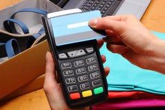 Utilice el terminal del pago y la tarjeta de crédito con la tecnología de NFC para pagar compras en tienda Imágenes de archivo libres de regalías