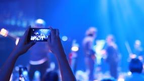 Utilice la mano toman la foto móvil en concierto imagenes de archivo