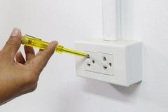 Utilice las manos para coger el probador de las tuberías de los destornilladores Foto de archivo