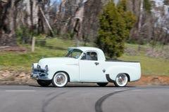 Utilidad 1956 de Holden FJ que conduce en la carretera nacional fotografía de archivo