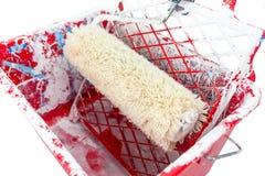 Utilisé, rouge, sale, le seau de peinture avec le rouleau de peinture se trouve sur la grille D'isolement sur un fond blanc avec  photographie stock libre de droits