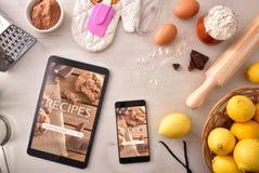 Utilisant l'appli numérique de livre de cuisine dans des dispositifs en pâtisserie images libres de droits
