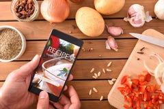 Utilisant l'appli numérique de livre de cuisine dans le smartphone pour la cuisson photo libre de droits