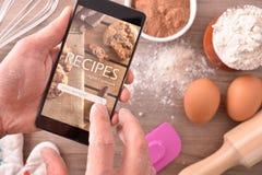 Utilisant l'appli numérique de recettes dans le mobile en pâtisserie photos stock