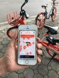 """Utilisant l'application sur l'iPhone pour la bicyclette de location de  d'""""mobike†qui se gare sur le sentier piéton près de  Photo stock"""