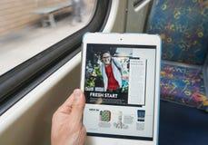 Utilisant l'iPad sur le train pendant la permutation photographie stock
