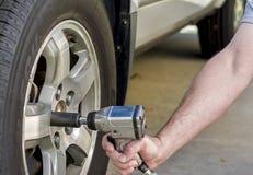 Utilisant la clé d'air pour enlever le pneu de voiture Photo stock