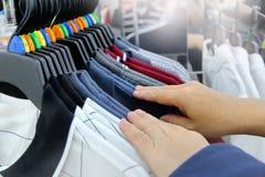 Utilisant la main pour choisir un ensemble de vêtements portez par couleur et classez photo stock