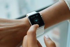 Utilisant la montre blanche d'Apple Photographie stock