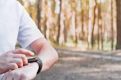Utilisant la montre intelligente dehors pour marcher ou pulser image stock