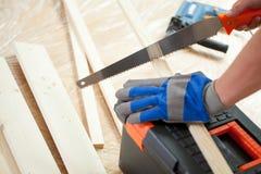 Utilisant la scie de main pendant la rénovation de maison Photo libre de droits