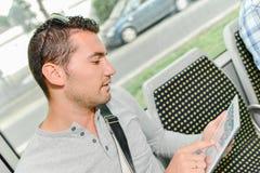 Utilisant la tablette pendant le journal permutez photo stock