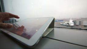 Utilisant la tablette sur le rebord de fenêtre à l'aéroport banque de vidéos