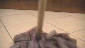 Utilisant le balai pour nettoyer un plancher de tuiles banque de vidéos