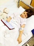Utilisant le comprimé sur le lit d'hôpital Images stock