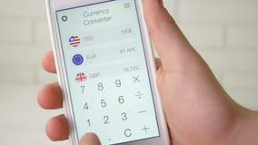 Utilisant le convertisseur APP de devise sur le smartphone banque de vidéos