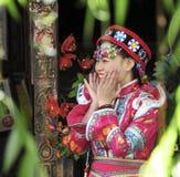 On utilisant le costume national de la femme de Naxi étant photographie Photographie stock libre de droits