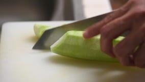 Utilisant le couteau de cuisine coupant la courgette sur le conseil blanc banque de vidéos
