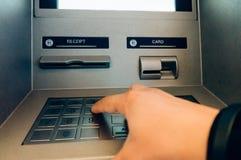 Utilisant le distributeur automatique de billets d'atmosphère Photo libre de droits