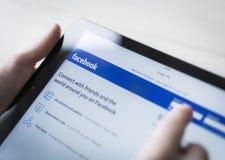 Utilisant le facebook sur Ipad ou PC de comprimé Image libre de droits