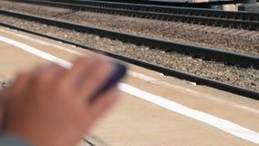 Utilisant le mobile tout en attendant le train sur la plate-forme banque de vidéos