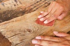 Utilisant le papier sablé frottez la planche en bois pour faire la table, meubles image libre de droits