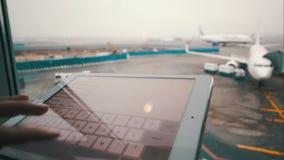 Utilisant le pavé tactile par la fenêtre à l'aéroport banque de vidéos