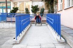 Utilisant le rampe de fauteuil roulant Photos libres de droits