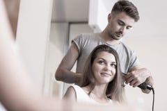 Utilisant le redresseur de cheveux Photographie stock libre de droits