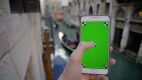 Utilisant le téléphone avec l'écran vert à Venise banque de vidéos