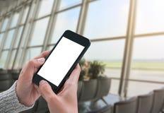 Utilisant le téléphone intelligent montrant l'écran blanc vide chez la main de la femme Photo libre de droits