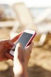 Utilisant le téléphone portable, écrivant des messages, wifi sur la plage en été Photographie stock libre de droits