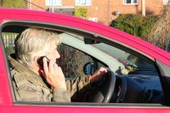 Utilisant le téléphone portable tout en pilotant. Image libre de droits