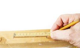 Utilisant le vieux mètre se pliant jaune pour mesurer le bois pour couper photos libres de droits