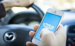 Utilisant Skype dans la voiture sur l'iphone Photo stock