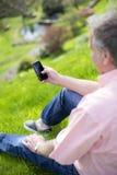 Utilisant Smartphone dans le jardin image stock