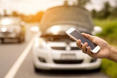 Utilisant un appel téléphonique de téléphone portable un mécanicien de voiture parce que la voiture était cassée photographie stock libre de droits