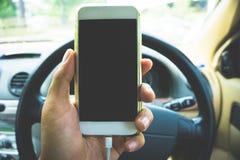 Utilisant un smartphone tout en conduisant une voiture Image libre de droits