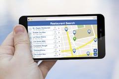 Utilisant un téléphone portable pour trouver un restaurant Photographie stock libre de droits