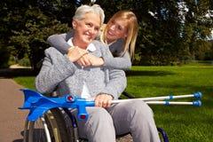 Utilisateur de fauteuil roulant heureux en stationnement Photo stock