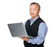 Utilisation asiatique d'homme d'ordinateur portable Photo stock