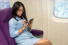 Utilisation asiatique de femme de téléphone portable à l'intérieur d'avion Photo libre de droits