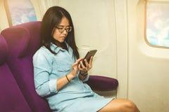 Utilisation asiatique de femme de téléphone portable à l'intérieur d'avion Photographie stock libre de droits